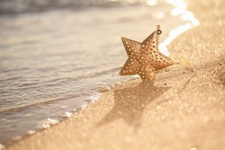 Christmas gold star decoration on the beach on a seascape backgound, summer Christmas and winter holyday concept, selective focus. Merry Christmas and Happy New Year background