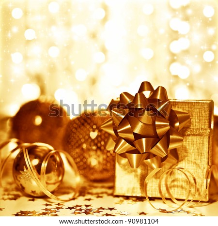 Christmas golden gift decorations, tree ball bauble ornament with present box over blur glowing bokeh lights background, home decor at winter holidays, new year eve