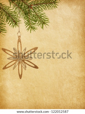 Christmas golden snowflake hanging on a spruce on paper background