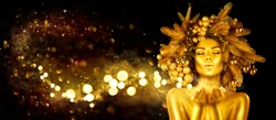 Christmas golden Woman. Winter girl pointing Hand, blowing blinking stars,  Beautiful New Year, Christmas Tree Holiday Hairstyle and gold skin Makeup. Gift. Girl in decorated Xmas wreath. Beauty Model