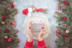 Christmas gray grunge background, fir twigs, berries, snowflakes, baubles, top view. New Year table setting menu decoration. Hands in red pullover hold tiny shopping basket, economy, poorness, misery