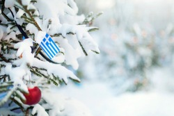 Christmas Greece. Xmas tree covered with snow, decorations and a flag of Greece. Snowy forest background in winter. Christmas greeting card.