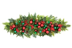 Christmas green & red bauble decoration with winter greenery of holly, ivy, mistletoe, cedar cypress & pine cones  on white background. Festive composition for the holiday season.