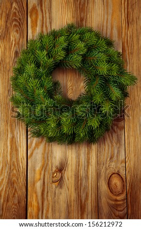 Christmas green wreath from firs brunches without decoration on wooden background with copy space.