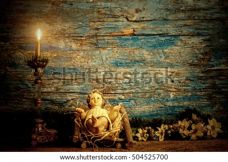 Christmas greeting card, baby Jesus in his crib and vintage candle, rustic wooden background with copy space for text