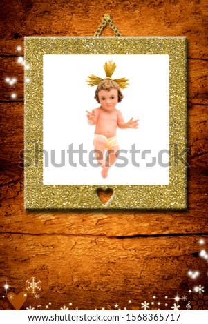 Christmas greeting card, Baby Jesus vintage figurine in gold picture hanging on a wooden wall.