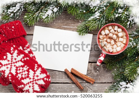 Christmas greeting card, fir tree, mittens and hot chocolate on wooden table. Top view with copy space #520063255