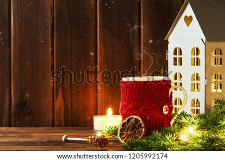 Christmas greeting card frame with place for your text design. Bright red cocoa cup, crystall brown sugar, orange slices, a burning candle, a branch of Christmas tree, house on wooden of boards. Snow