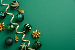 Christmas greeting card mockup. Elegant Xmas baubles and golden decorations on green background. Flat lay, top view.
