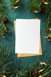 Christmas greeting card mockup with pine tree branches and golden tape on green background