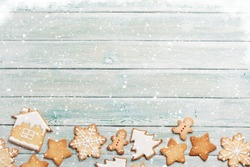 Christmas greeting card with gingerbread cookies over wooden backdrop. Top view with space for your greetings