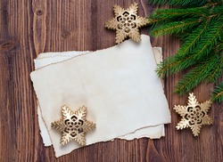 Christmas greeting card with old blank paper sheet, fir and snowflakes, wooden background