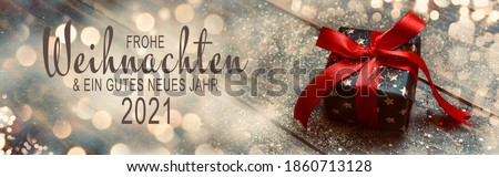 Christmas greeting card with text in German -  Frohe Weihnachten means Merry Christmas and Happy New Year 2021 - Gift box with red bow Stockfoto ©