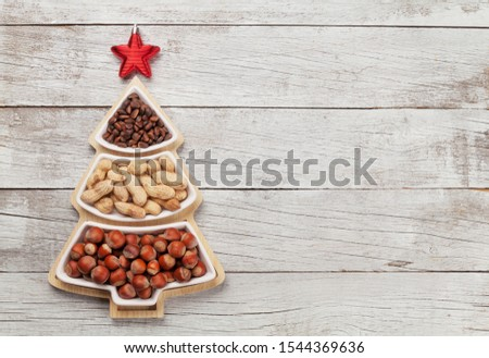 Christmas greeting card with various nuts in fir tree shaped box and copy space for your greetings. Top view flat lay #1544369636