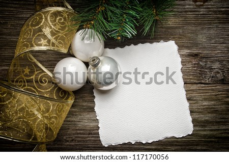 Christmas greeting card with white ornaments and golden ribbon