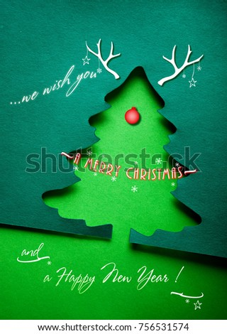 Christmas greeting card with xmas tree paper cutout. With seasons greetings as text and decorative elements with mock reindeer. Simple duotone composition #756531574