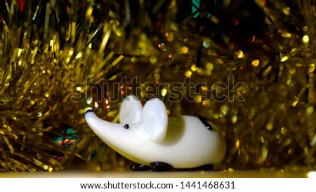 Christmas greeting from a rat or mouse. Happy Chinese New Year year of rat. The symbol of the New Year on the background of golden garland ornaments. Christmas Rat