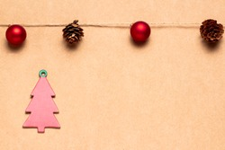 Christmas greetings card with a garland of balls and pineapples and red cardboard tree. Space for copying. Advertising banner
