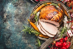 Christmas ham served with roasted vegetables and festive decorations on vintage background, top view, place for text. Christmas recipes and dishes concept