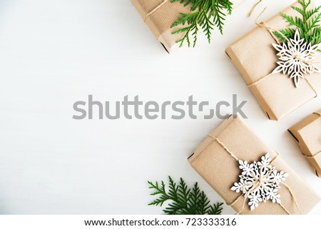 Christmas handmade gift boxes decorated with craft paper and white snowflakes on white wooden background top view. Merry christmas greeting card. Winter xmas holiday theme. Happy New Year. Flat lay. #723333316