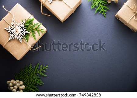 Christmas handmade gift boxes decorated with craft paper, branch and snowflake on dark background top view. Merry christmas greeting card, frame. Winter xmas holiday theme. Happy New Year. Flat lay