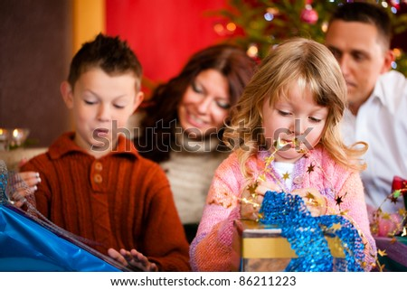 Christmas - happy family (parents with son and daughter) with gifts on Xmas Eve