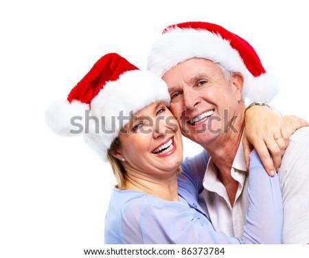 Christmas. Happy senior couple  with santa caps . Isolated over white background.