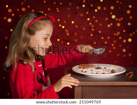 Christmas - happy smiling six years old blond caucasian child girl decorating cookies plate on dark red background with lights