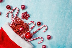 Christmas hat of Santa Claus, with Christmas candies, toys and sequins on a blue background. Minimal Christmas concept. Caramel cane. Copy of the text space.