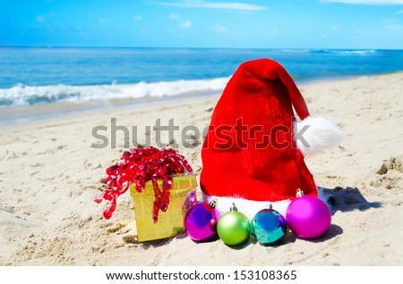 Christmas hat with gift box and christmas balls on the beach by the ocean - holiday concept