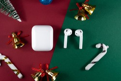christmas headphones. Air Pods. with Wireless Charging Case. New Airpods 2020 on green background. Air Pods on Christmas background.wireless headphones with Christmas toys