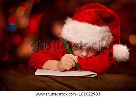 Christmas helper child writing letter to Santa Claus letter in red hat stock photo