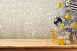 Christmas holiday background with Christmas tree and decorations on wooden table. Black, golden and silver ornaments