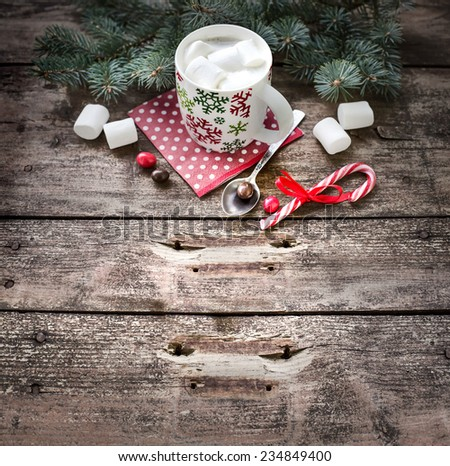 Christmas holiday background with coffee cup,fir and candy canes on dark rusty wooden table