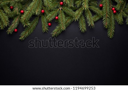 Christmas holiday background with copy space for advertising text. Fir branches and holly berries on black. Flat lay, top view