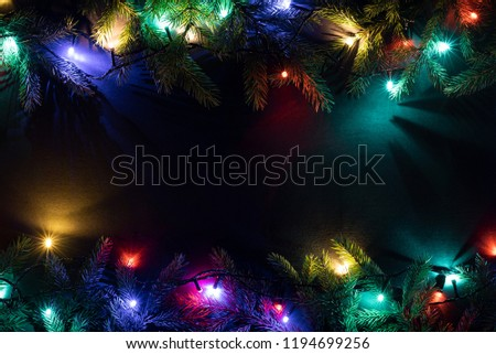 Christmas holiday background with copy space for text. New Year concept. Glowing garland and decor of fir branches. Flat lay, top view