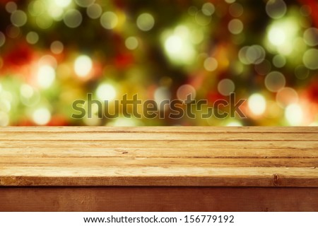 Christmas holiday background with empty wooden deck table over festive bokeh. Ready for product montage