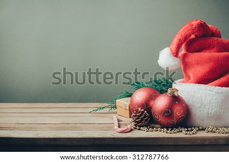 Christmas holiday background with Santa hat and decorations. Retro filter effect - Shutterstock ID 312787766