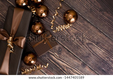 Christmas holiday composition, ornament. Festive creative gold pattern, spruce branches, xmas tree, xmas golden decor holiday ball with gift and ribbon on wooden brown background. Flat lay, top view. #1447405589