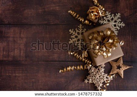 Christmas holiday composition, ornament. Festive creative gold pattern, spruce branches, xmas tree, xmas golden decor holiday ball with gift and ribbon on wooden brown background. Flat lay, top view. #1478757332