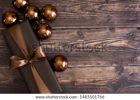 Christmas holiday composition, ornament. Festive creative gold pattern, spruce branches, xmas tree, xmas golden decor holiday ball with gift and ribbon on wooden brown background. Flat lay, top view. #1483501766