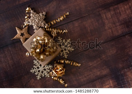Christmas holiday composition, ornament. Festive creative gold pattern, spruce branches, xmas tree, xmas golden decor holiday ball with gift and ribbon on wooden brown background. Flat lay, top view. #1485288770