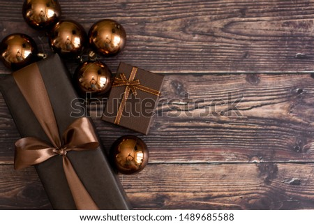Christmas holiday composition, ornament. Festive creative gold pattern, spruce branches, xmas tree, xmas golden decor holiday ball with gift and ribbon on wooden brown background. Flat lay, top view. #1489685588