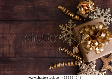 Christmas holiday composition, ornament. Festive creative gold pattern, spruce branches, xmas tree, xmas golden decor holiday ball with gift and ribbon on wooden brown background. Flat lay, top view.