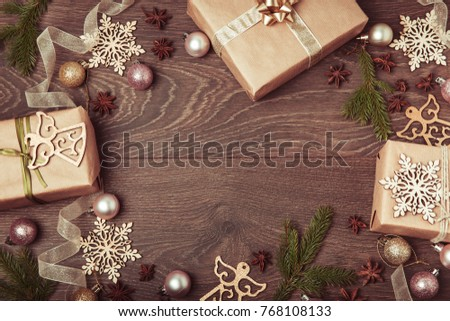 Christmas holiday composition, ornament. Festive creative gold pattern, spruce branches, xmas tree, xmas golden decor holiday ball with gift and ribbon on wooden brown background. Flat lay, top view #768108133