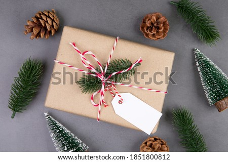 Christmas holiday composition with gift box having label decoration, new year and xmas or anniversary with presents having tag on cement floor background in season, top view or flat lay, copy space.