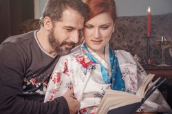 Christmas holiday concept: Young married couple reading a book on a winter's night