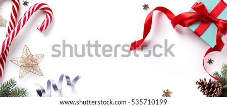 Christmas holiday Decoration element; Christmas  border with fir tree branches and Christmas ornament on white background. Flat lay, top view.