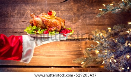 Christmas Holiday dinner. Santa Claus hand holding roasted Chicken. Christmas and New Year food concept, over rural wooden background