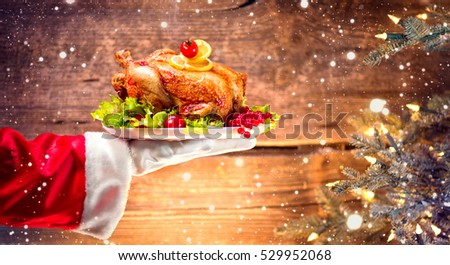 Christmas Holiday dinner. Santa Claus hand holding roasted Chicken. Christmas and New Year food concept, over rural wooden background and Decorated Christmas tree with lights